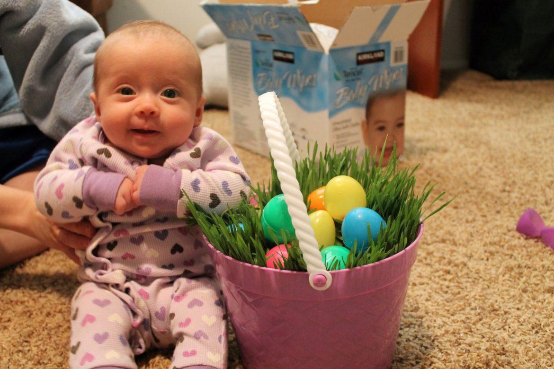 A baby sitting near a DIY Easter Grass Basket