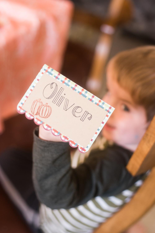 """A little boy holding \""""Oliver\"""" named card"""