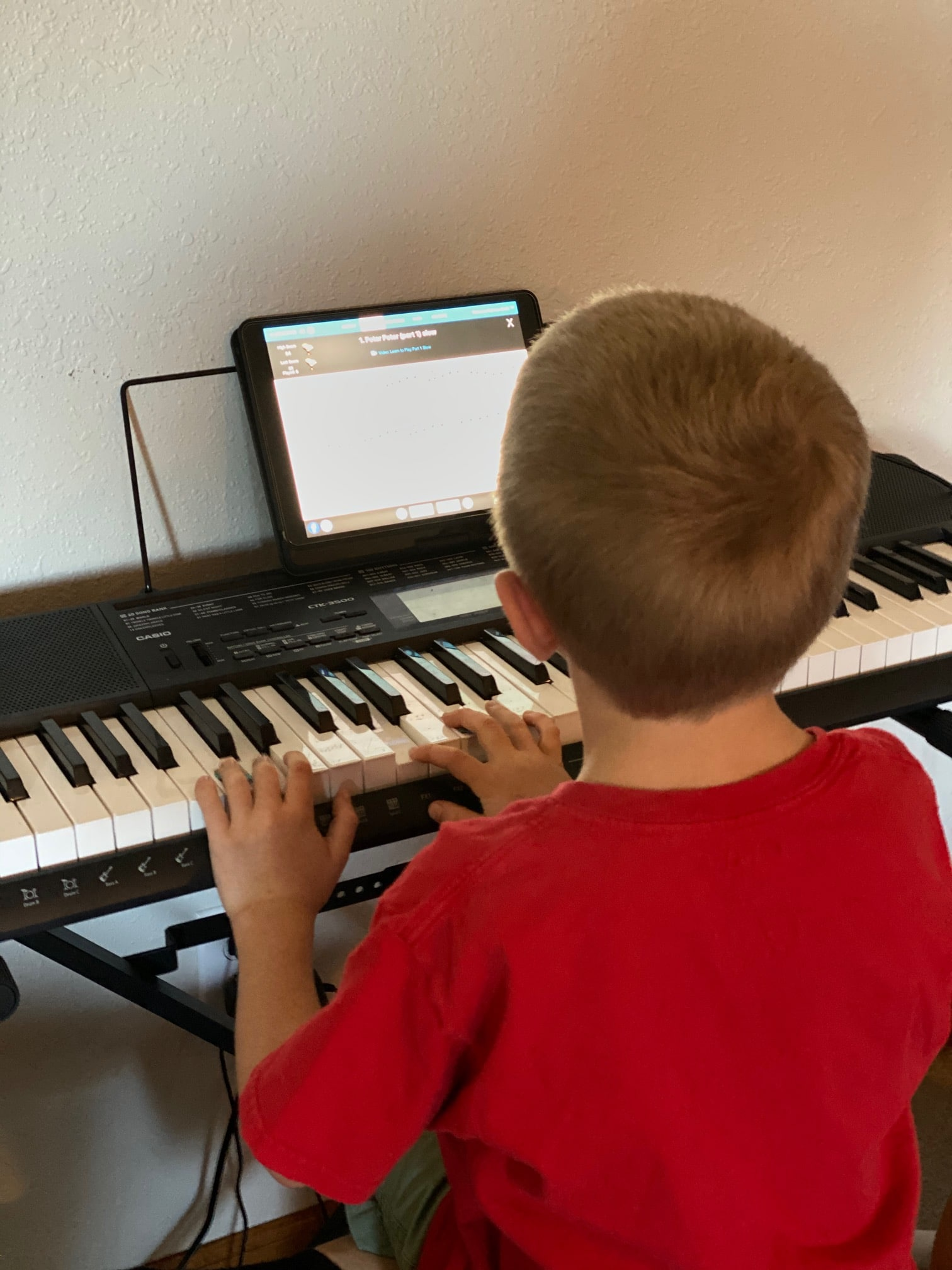 A boy sitting at a desk in front of a piano keyboard playing piano marvel