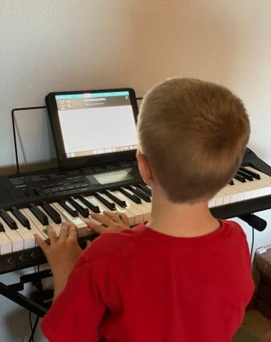 A boy sitting at a desk in front of a piano keyboard
