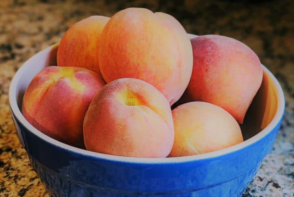 A blue bowl filled with peaches