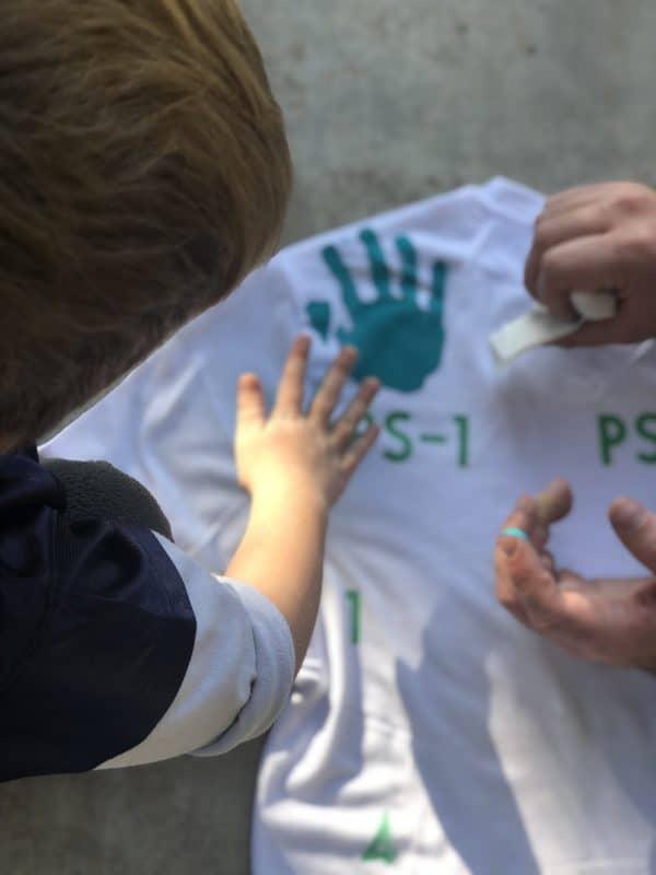 little boy putting hand print on shirt