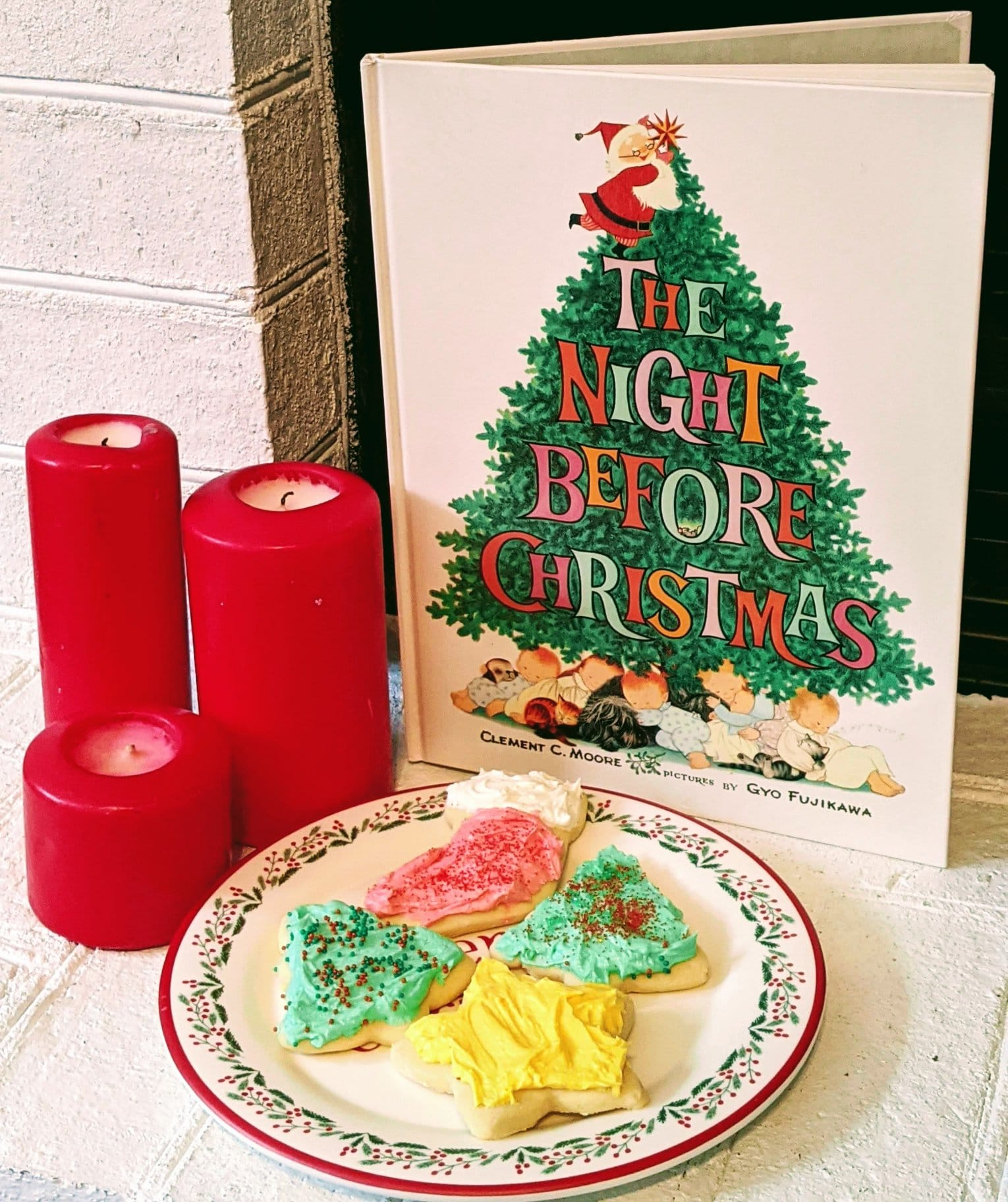 frosted sugar cookies in ront of Christmas book