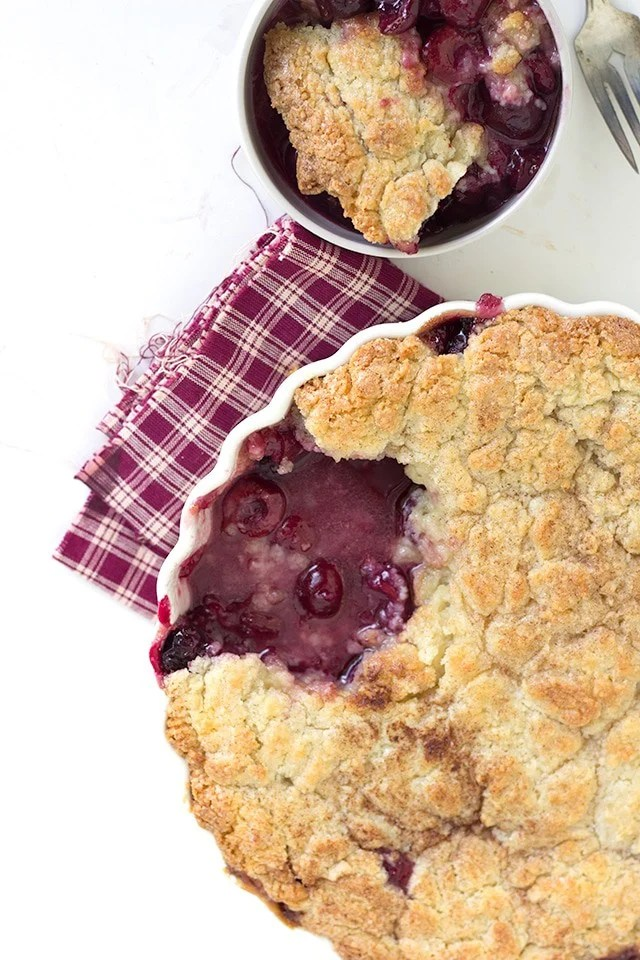 overhead image of a fresh cherry cobbler with sugar cookie topping. One serving sits in a white ramekin above it