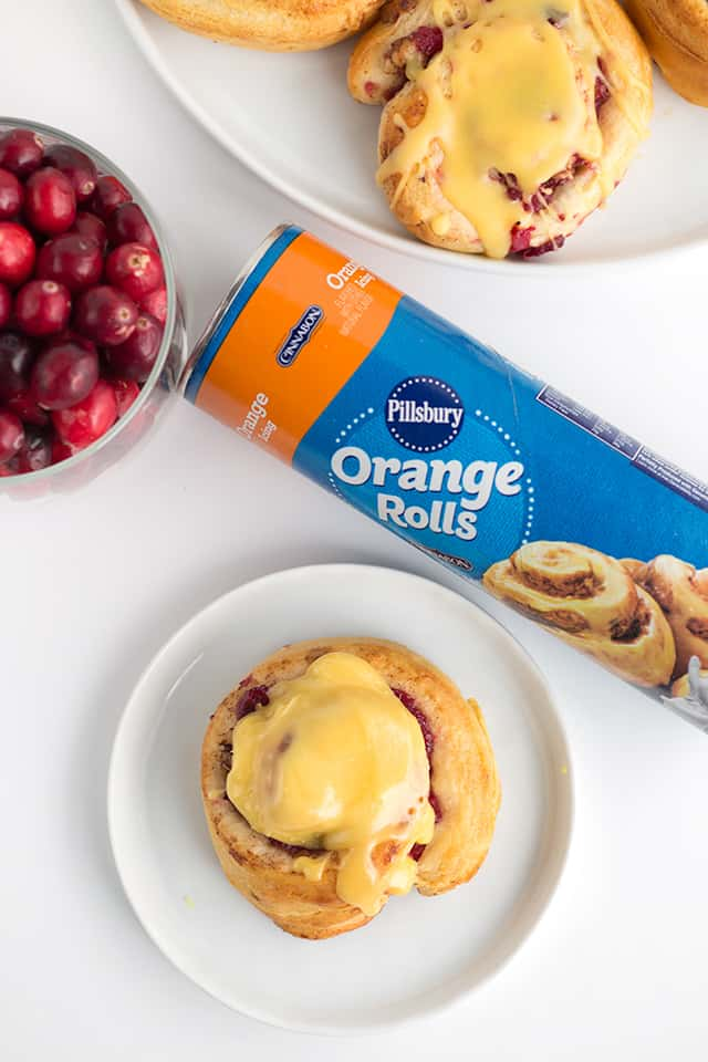Showing cranberry orange cinnamon rolls from above with a package of store-brought orange rolls