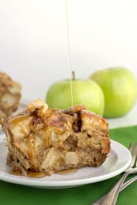 Slice of apple cinnamon french toast with maple syrup being poured on top of it.