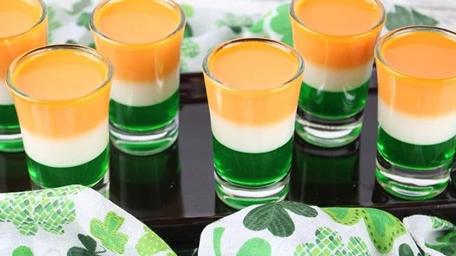 St. Patrick's Day Jello Shots staggered on a black plate with a shamrock fabric