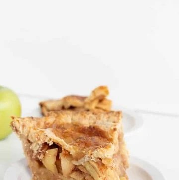 a slice of apple pie with cheddar cheese crust on a white plate