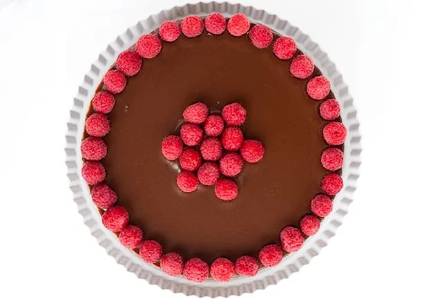 horizontal shot of chocolate raspberry cheesecake on a white cake plate with a white background