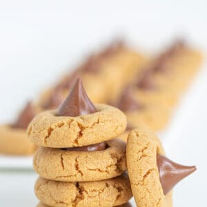 Stack of Peanut Butter Blossom Cookies with another cookie on its side leaned against the stack
