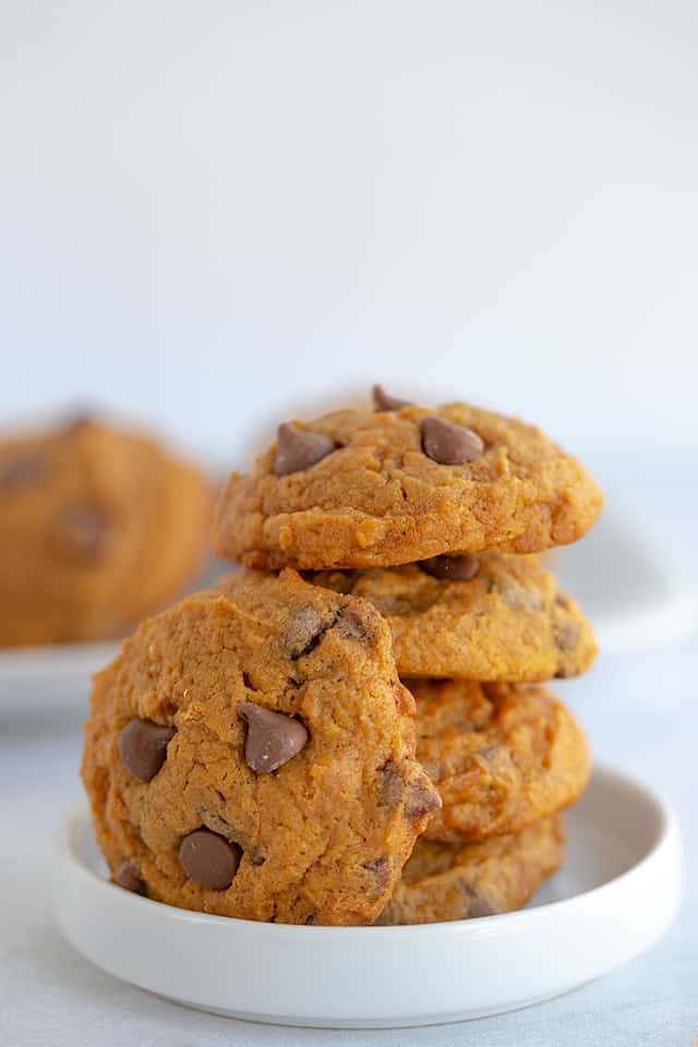 stack of pumpkin pudding cookies with a cookie leaned against them on a white plate