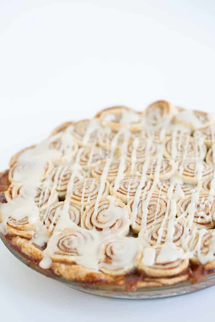cinnamon roll apple pie in a glass pie dish on a white surface