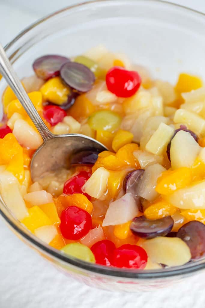 bowl full of fruit salad with a serving spoon in it