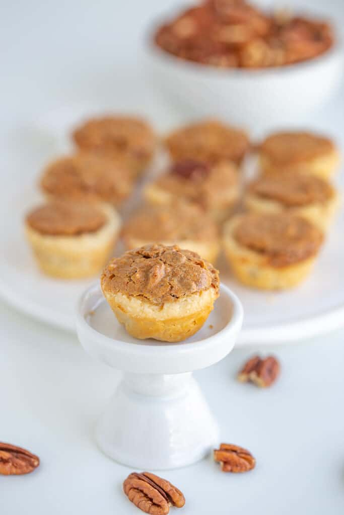 a pecan tassie on a cupcake stand with a platter of tassies behind it and pecans below it