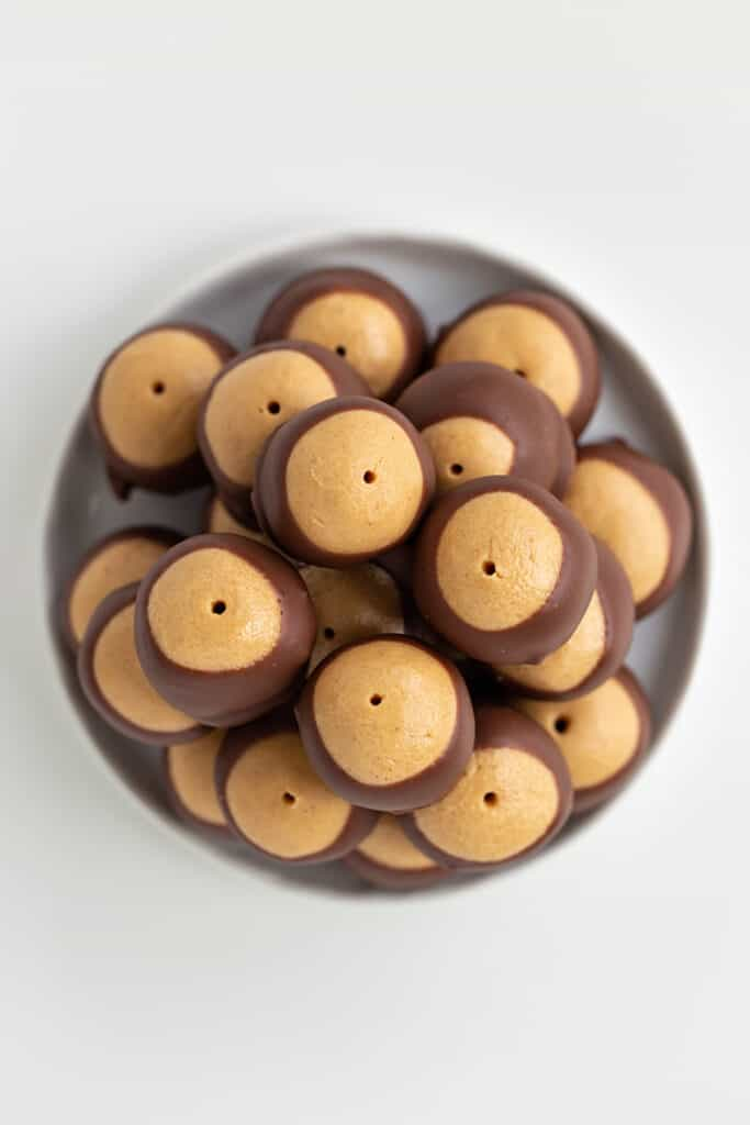 overhead photo of stacked buckeyes on a white plate on a white surface
