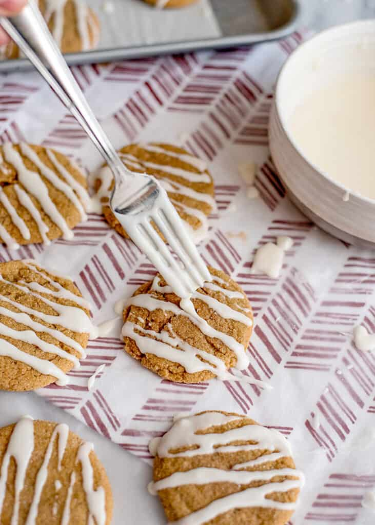 adding icing to cookies on a red and white fabric with a fork