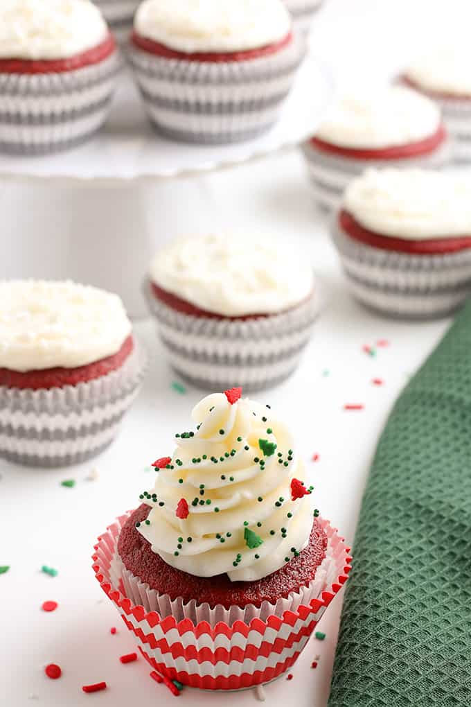 Christmas decorated cupcake with festive sprinkles on a white background with a green linen beside the cupcake