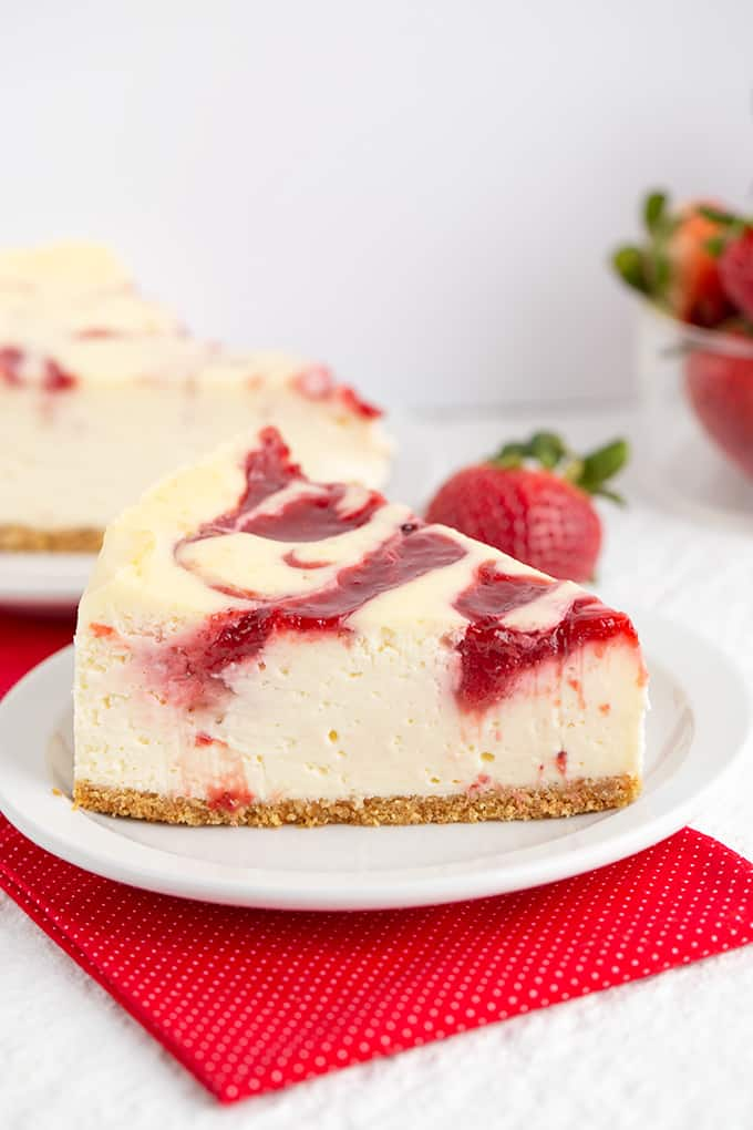 Strawberry cheesecake on a white plate with a red fabric under it and strawberries behind it