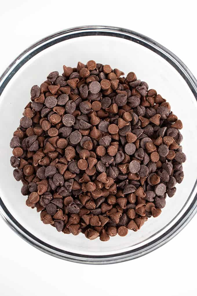 a glass bowl full of chocolate chips