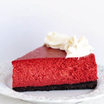 slice of red cheesecake on a white plate on a white background