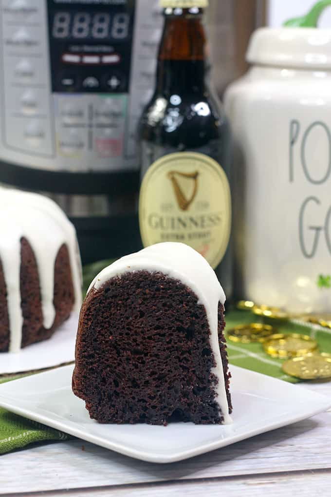 slice of bundt cake on a white dessert plate with an pressure cooker and bottle of beer behind it