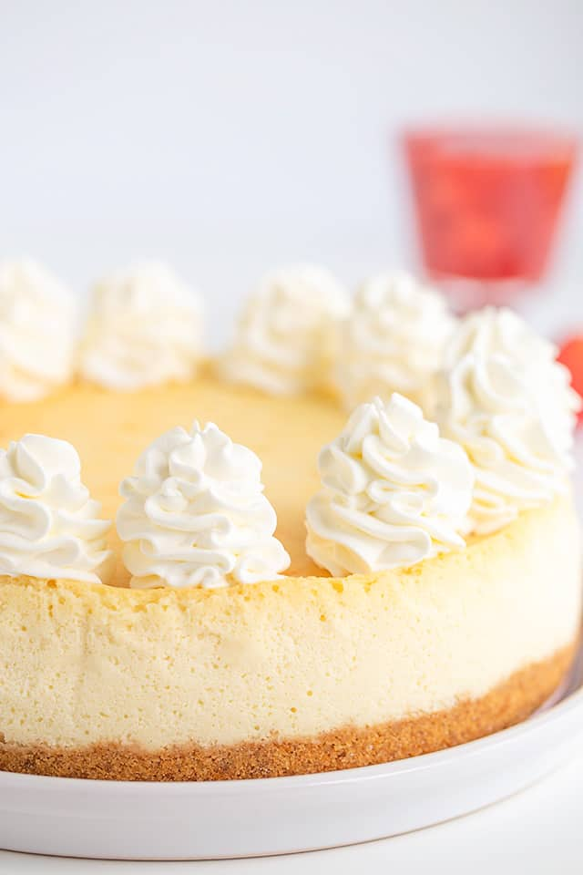 a whole cheesecake on a white plater with a white background and strawberry sauce behind it