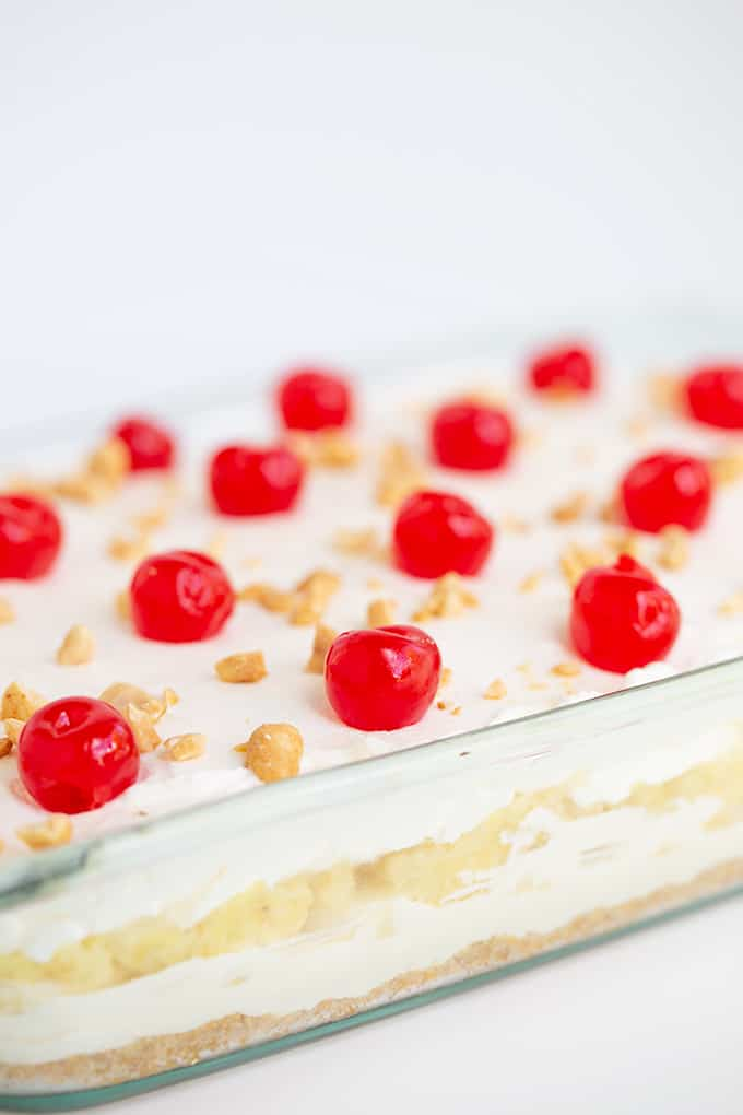 a glass pan full of a dessert with the layers showing on the side of the pan and the maraschino cherries in focus