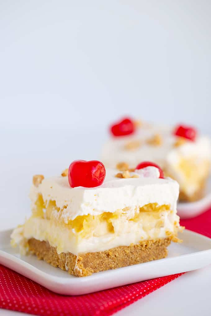 slice of banana split cake on a white square plate with a red linen under it