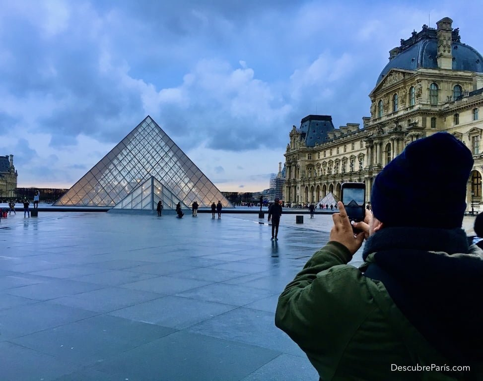 tourist taking picture of the Louvre Pyramid
