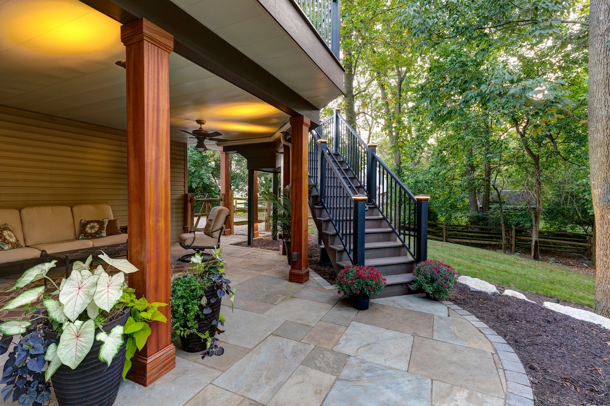 Adding A Patio Under Your Deck Tips And Ideas For Homeowners In | Patio With Stairs From House | Residential | Curved Paver | Main Entrance Stamped Concrete Front | Walkout Basement | Decorative