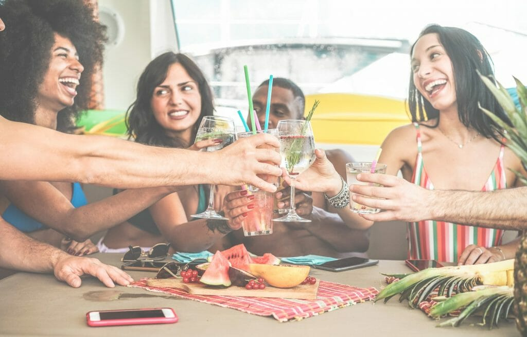 Happy friends cheering with tropical cocktails in boat party - Young people having fun in summer ship vacation - Youth lifestyle, friendship and holiday concept - Main focus on hands glasses