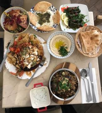 Fait Maison Salon de th       Table spread with Middle eastern dishes