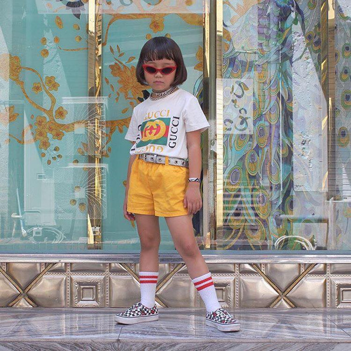 The Most Fashionable Kids to Follow on Instagram kid wearing gucci logo t shirt and yellow shorts