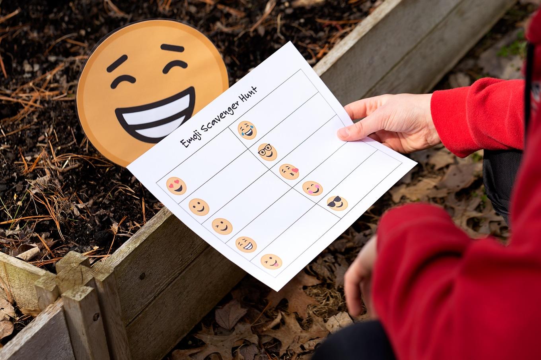 Child Holding Paper That Reads Emoji Scavenger Hunt