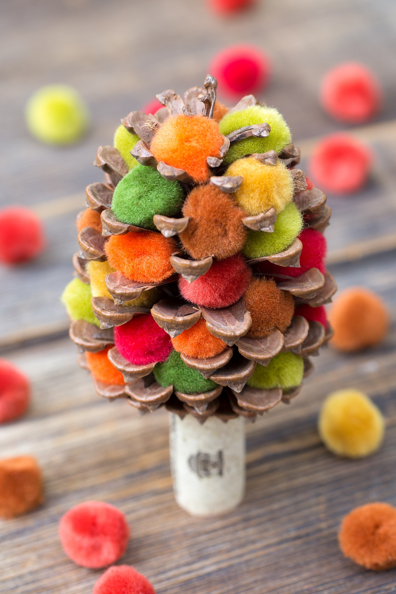 Learn how to make a colorful fall pine cone tree with pine cones, corks, and pom poms. This easy fall nature craft is perfect for kids of all ages!