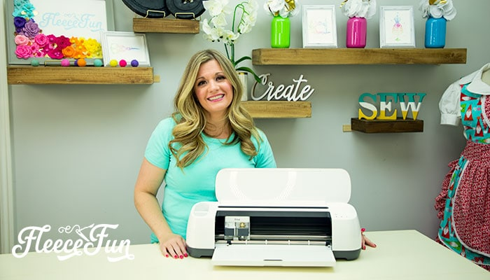 Me standing with a Cricut Maker. Get your Top 3 Cricut Maker Questions Answered!  What Makes the Cricut Maker different from other machines? Is Design Space easy to use? What exactly can you make with a Cricut Maker? Get the detailed answers you need!