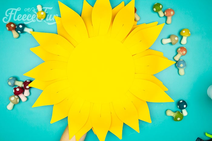 Glue back onto sunflower. This Giant Paper Sunflower DIY (FREE SVG files) is perfect for fall! Make a Giant flower wall or use it to decorate your space! So many possibilities!