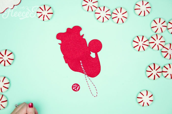 Adding the hanger. Items needed. With a Free Ornament Template you can make this adorable felt Santa! This homemade ornament is no sew and makes for a wonderful gift.