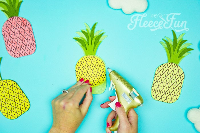 gluing the last item on. This DIY Pineapple décor is easy to make and has many possibilities! Use the free files to make anything from a cute shirt using HTV to a pillow using fabric. There is something magical about pineapples. They brings feeling of warmth, vacation and fun!
