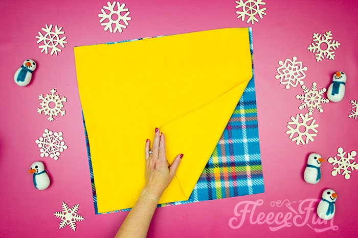 fabric layered on top of eachother. Learn how to make a No Sew Fleece Tie Blanket 3 different ways. Never before seen techniques and FREE templates to make it fast and easy.