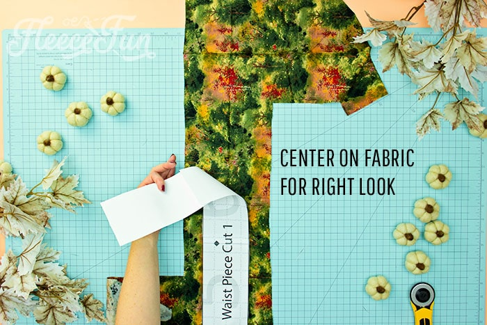 Picture of waist pattern being cut out and how to center on fabric for correct look. This Free apron pattern and tutorial includes a pdf pattern and video! Make a vintage style apron that is chic.