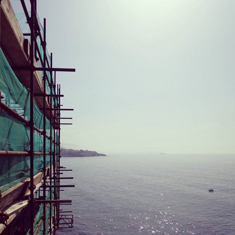 Facing the sea with spring blossoms. Scaffolding...