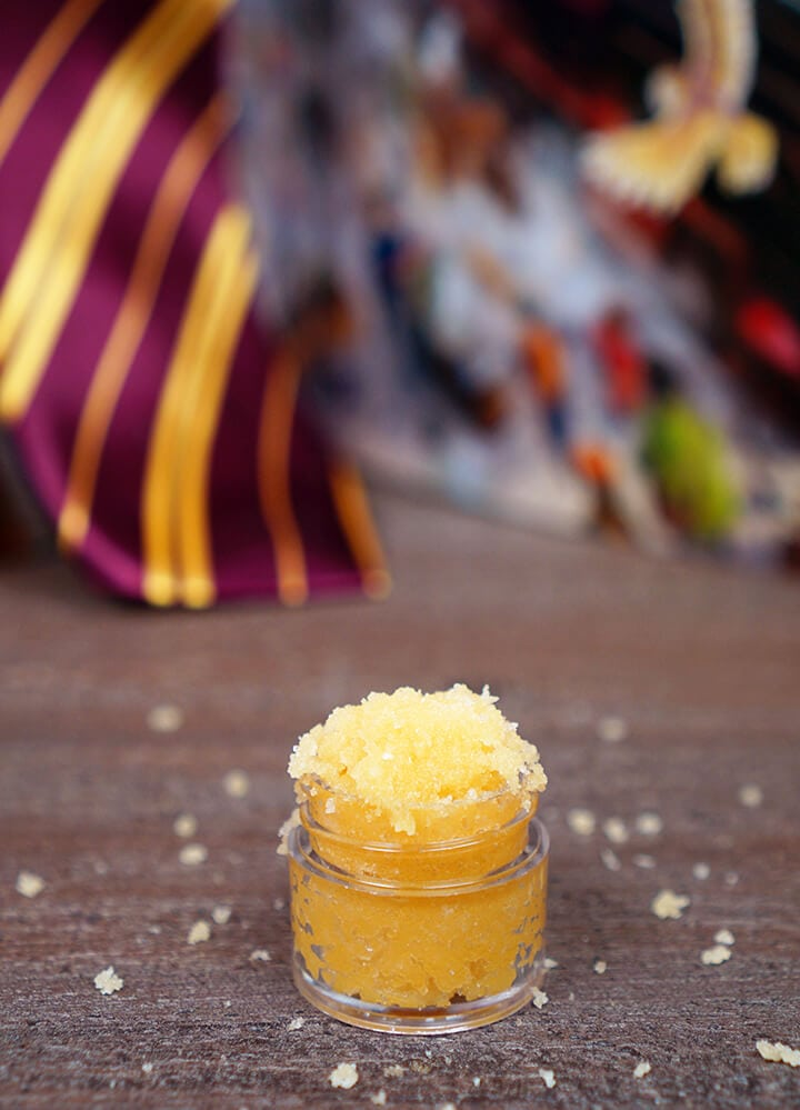 Small jar of Butterbeer sugar scrub on wood background with Harry Potter book and Gryffindor tie in background