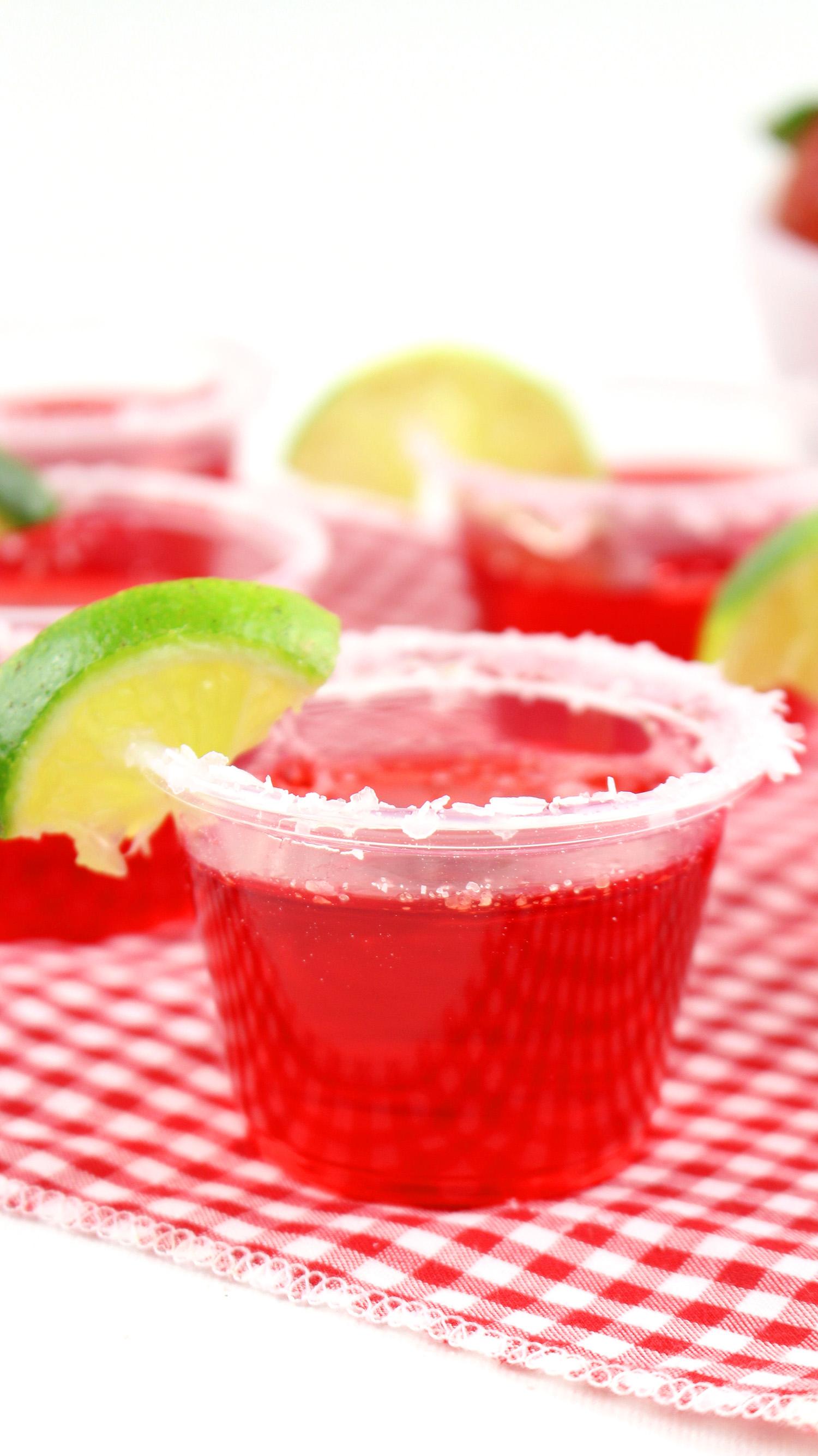 strawberry margarita jello shots with a lime garnish