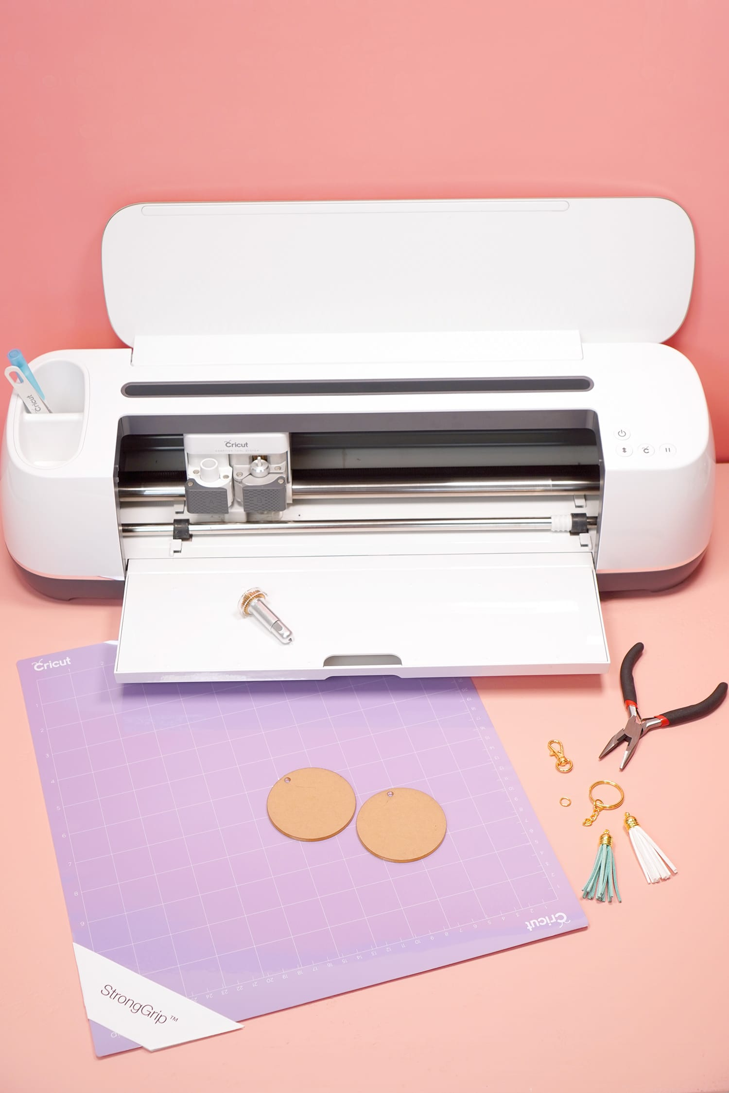 Cricut Maker machine and supplies needed to make an engraved acrylic keychain with the Cricut Engraving Tool