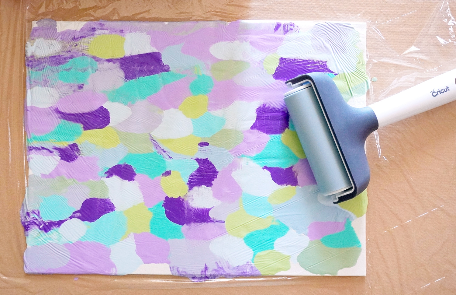 Blobs of paint on a canvas covered in plastic wrap with a brayer on top