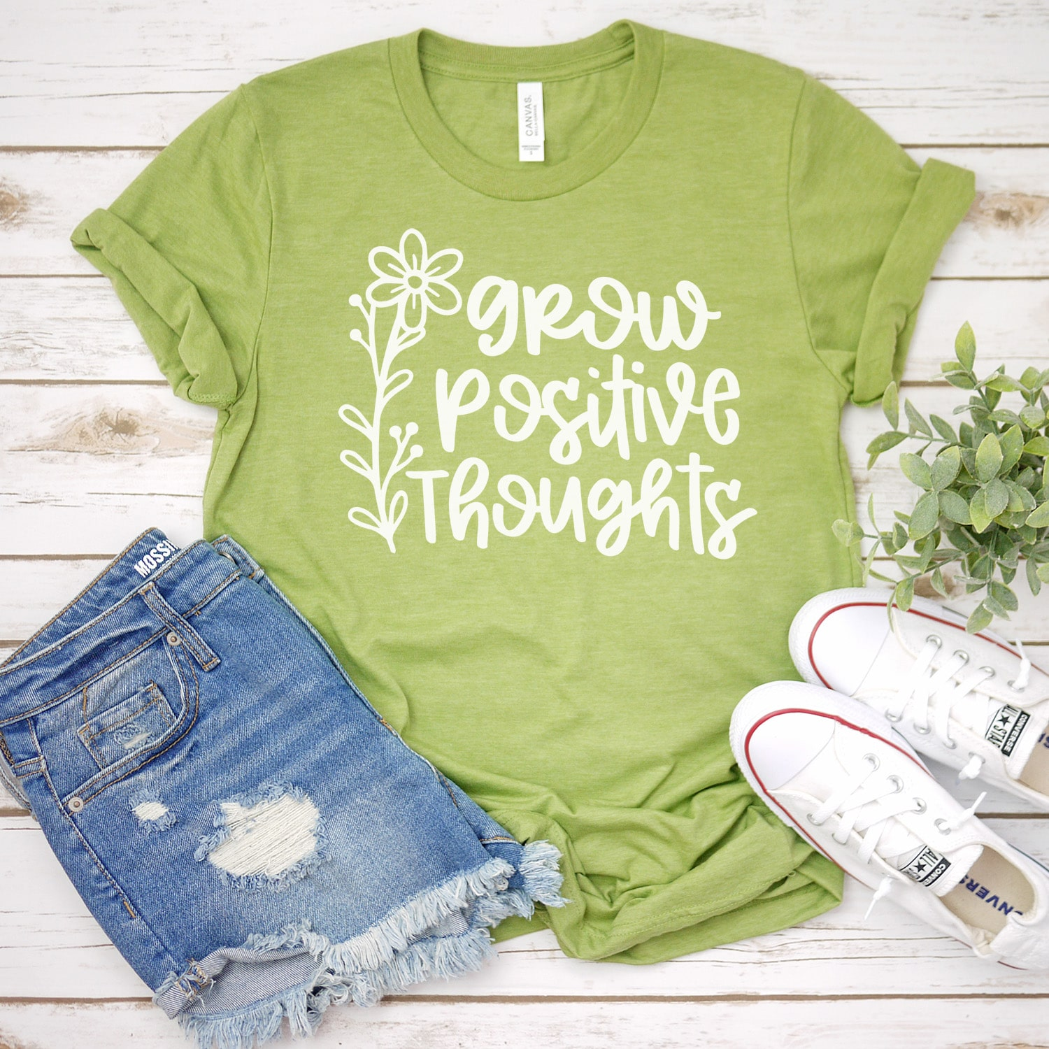 Green t-shirt featuring grow positive thoughts message across front, with white shoes and blue jean shorts