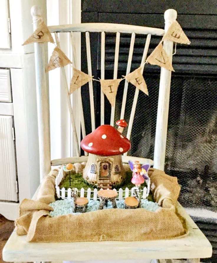 Red mushroom shaped fairy garden house with fairy figurine in burlap lined box sitting on a white wood chair