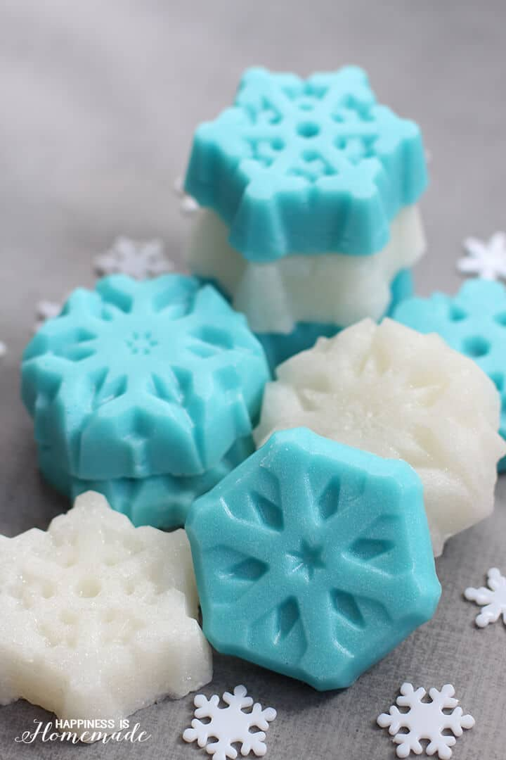 Blue and white snowflake shaped sugar scrub cubes on a grey background