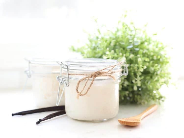 Jar of vanilla sugar scrub with spoon and vanilla bean